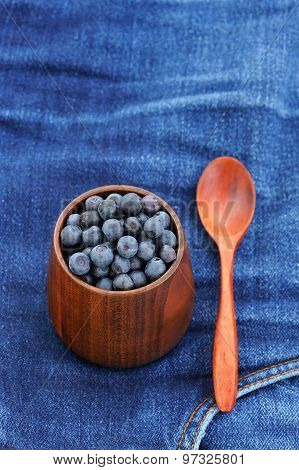 Fresh Wild Blueberries In Wooden Vase With Wooden Spoon On Frayed Indigo Jeans