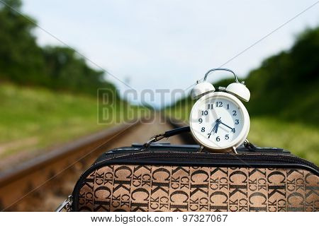 Clock Is Standing On Suitcase