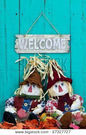 Scarecrows sitting under welcome sign with fall decor