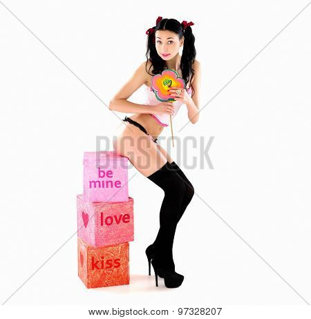 Amazing sexy smiling woman in bikini with big candy lollipop and pink boxes