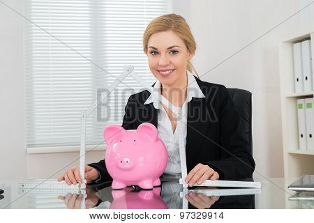 Businesswoman With Ruler Folded In House Shape And Piggy Bank