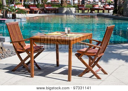 Table And Chairs In Empty Cafe Next To The Pool
