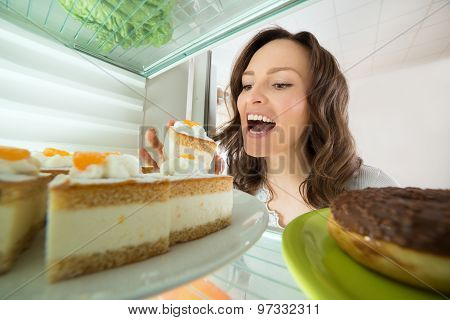 Woman Eating Slice Of Cake From Fridge