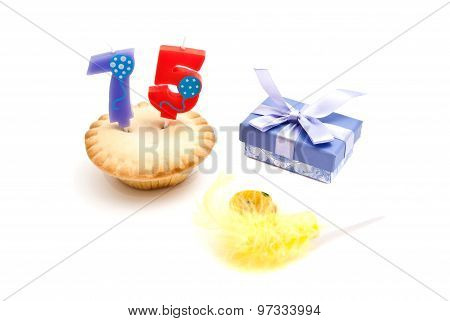 Cupcake With Seventy Five Years Birthday Candle, Gift And Whistle On White