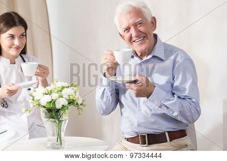 Nurse And Retiree Drinking Coffee
