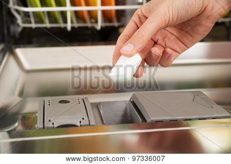 Person Hands Putting Dishwasher Tablet In Dishwasher Box