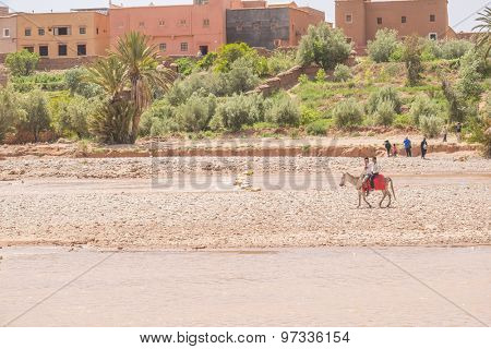 AIT BENHADDOU, MOROCCO - APRIL 10, 2015:  Local boys ride a donkey on riverside near old town of Ait Benhaddou
