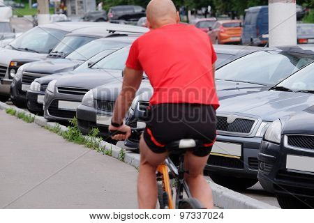 Cyclist drives by the cars on a parking