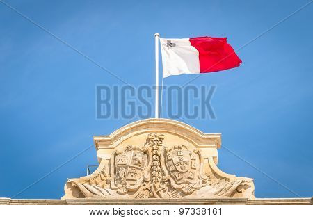 Maltese White And Red Flag Against A Blue Sky - Top Of Prime Minister Building Parliament