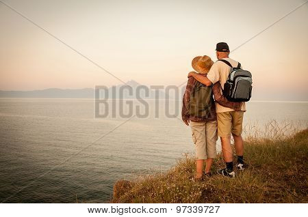 Woman and man hugging on the top of the mountain in the sunset