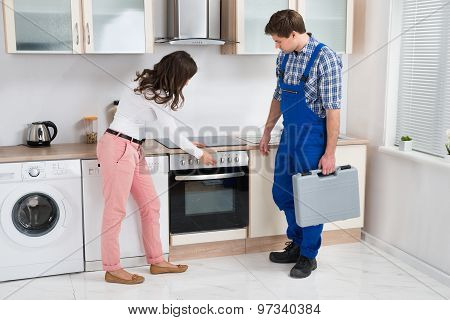 Housewife Showing Damaged Oven To Worker