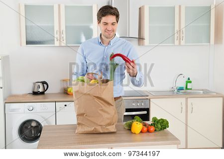 Man With Grocery Bag In Kitchen Room