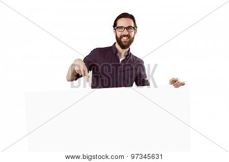 Handsome hipster showing large poster on white background
