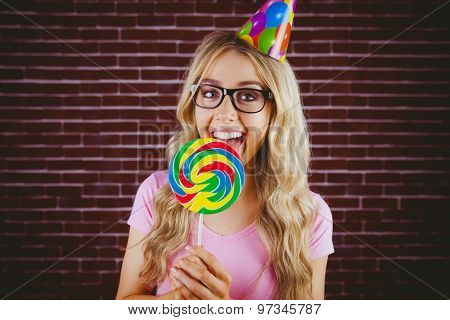 A beautiful hipster with party hat holding a giant lollipop against a red brick wall