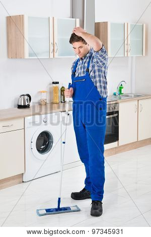 Worker Cleaning Floor With Mop