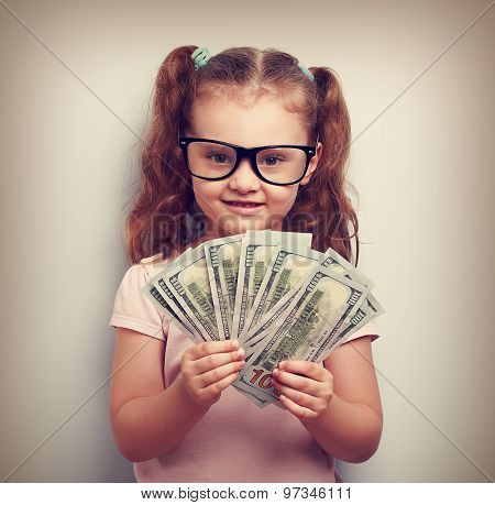 Happy Kid Girl In Glasses Holding Money In The Hand And Looking With Smile. Vintage Portrait