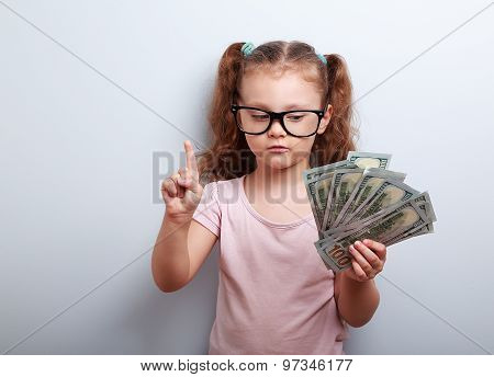 Small Kid Girl Holding Dollars And Have An Plan How Earning Much Money In Crisis. Serious Child.
