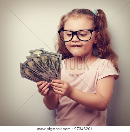 Thinking Fun Small Kid Girl In Glasses Counting Money In The Hands. Vintage Closeup Portrait