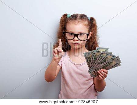Cute Kid Girl Holding Dollars And Have An Idea How Earning Much Money In Crisis. Serious Child Teach