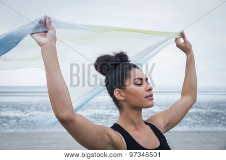 Fit girl standing with scarf blowing in wind at the beach