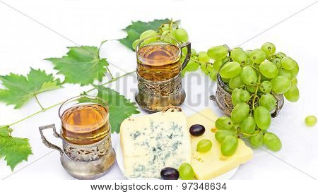 White wine, cheese and grapes on table
