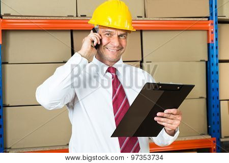 Businessman With Clipboard Using Mobile Phone