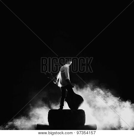The guitarist playing on large electric guitar in a great smoke, rock concert stage.