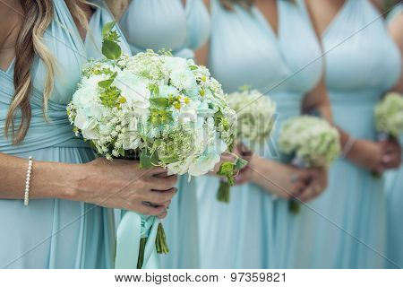 Closeup of bridesmaids holding flowers at the wedding day
