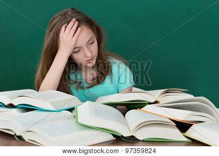 Schoolgirl With Open Books In Classroom