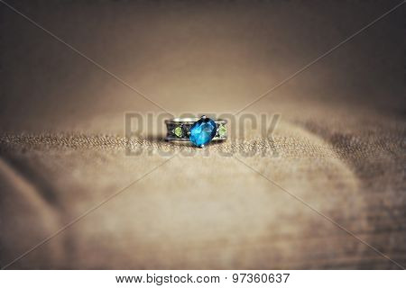 Unique wedding engagement ring on a fabric surface with a emerald gemstone