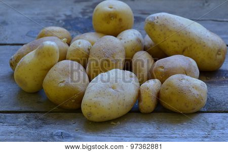 Homegrown potatoes on wooden background