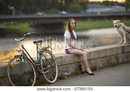 Cute young girl with a bicycle and a dog sitting on the promenade in the soft sunset light.