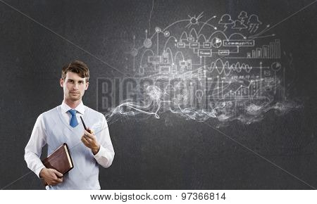 Handsome young businessman thinking over ideas and smoking pipe