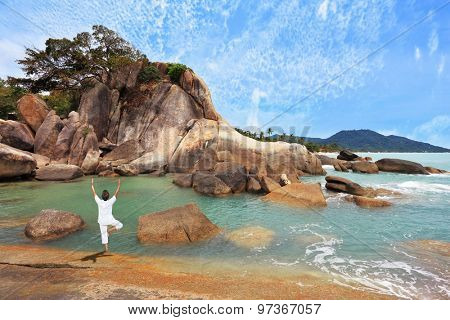 Gorgeous beach on the Andaman Sea. Middle-aged woman dressed in white doing yoga. 
