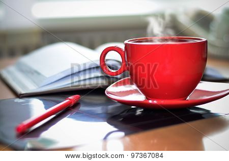Red cup of hot coffee notepad and pencil on the desktop
