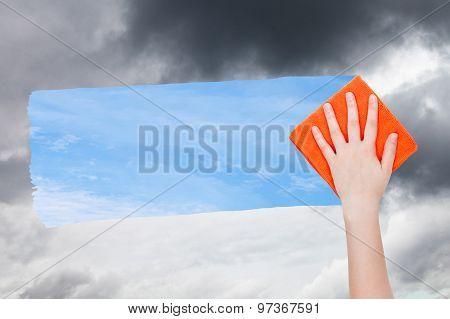 Hand Deletes Dark Clouds By Orange Cloth