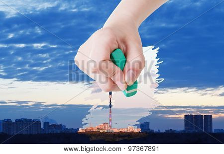 Hand Deletes Sunrise Over City By Rubber Eraser