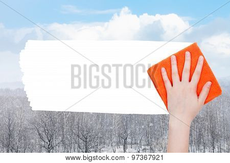 Hand Deletes Snow Over Forest By Orange Rag