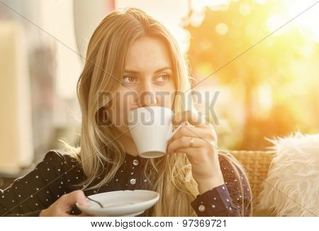 Beautiful blonde female drink coffee in cafe