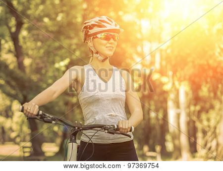 Beautiful woman in helmet and glasses stay on the bicycle.