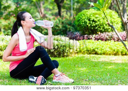 Asian Chinese woman drinking water after sport in park