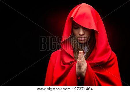 beautiful woman with red cloak in studio praying