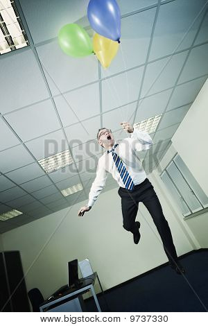 Businessman Flying In Office With Balloons