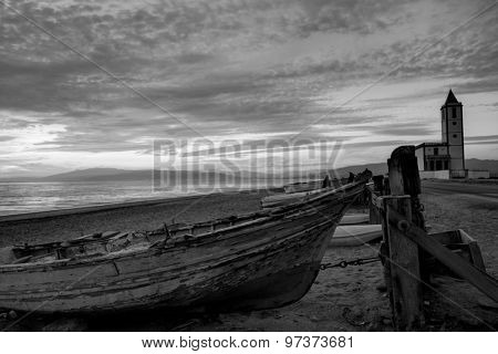 Cabo de Gata in Almeria at San Miguel Beach and Salinas church with stranded boats at sunset