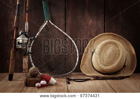 Vintage still life. Fishing poles, bobbers, hat and net.  Focus on Bobbers in foreground.