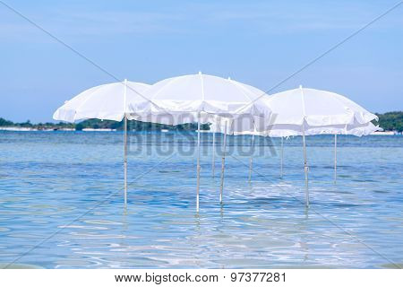 White Umbrella On Summer Tropical Beach With Sailing Boat.