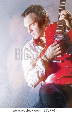 Music Concepts. Portrait Of Young Male Guitar Player Performing With Guitar Against Gray. Mixed Ligh