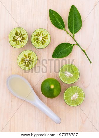 Fresh Lime Juice And Lime Slice On Wooden Background With Lime Leaf.