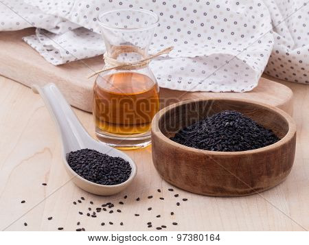 Black Sesame Oil And Sesame Seeds Set Up On Wooden Table