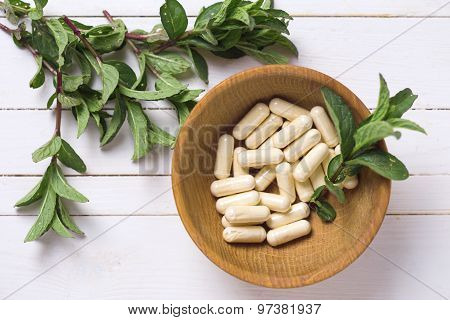 Pills  In Bowl And Leaves Of Mint On White Table.